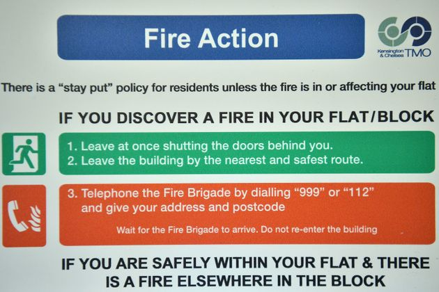 A fire safety action sign displayed inside a block near Grenfell