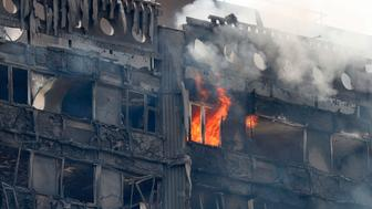 Flames and smoke continue to engulf Grenfell Tower, a residential block of flats in west London on June 14, 2017, as firefighters continue to control a fire that started in the early hours of the morning. At least six people were killed Wednesday when a massive fire tore through a London apartment block in the middle of the night, with witnesses reporting terrified people had leapt from the 24-storey tower. The tower was built as public housing and is located in a working-class but rapidly gentrifying part of the mostly wealthy Borough of Kensington and Chelsea. / AFP PHOTO / Adrian DENNIS        (Photo credit should read ADRIAN DENNIS/AFP/Getty Images)