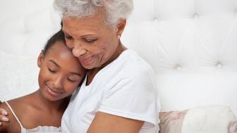 Older woman and granddaughter hugging
