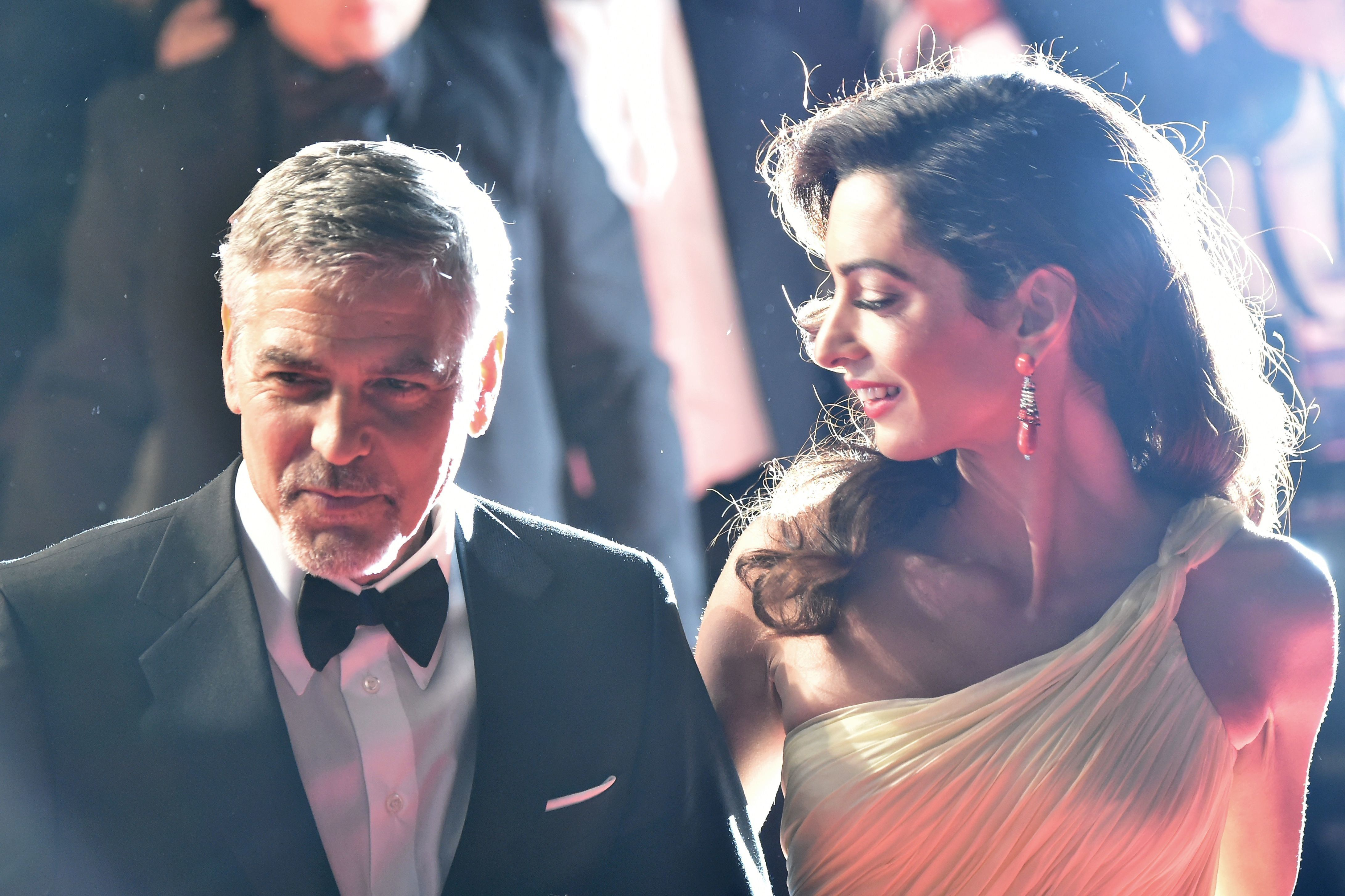 US actor George Clooney (L) and his wife, British-Lebanese lawyer Amal Clooney leave on May 12, 2016 the Festival Palace after the screening of the film 'Money Monster' at the 69th Cannes Film Festival in Cannes, southern France. / AFP / ALBERTO PIZZOLI        (Photo credit should read ALBERTO PIZZOLI/AFP/Getty Images)