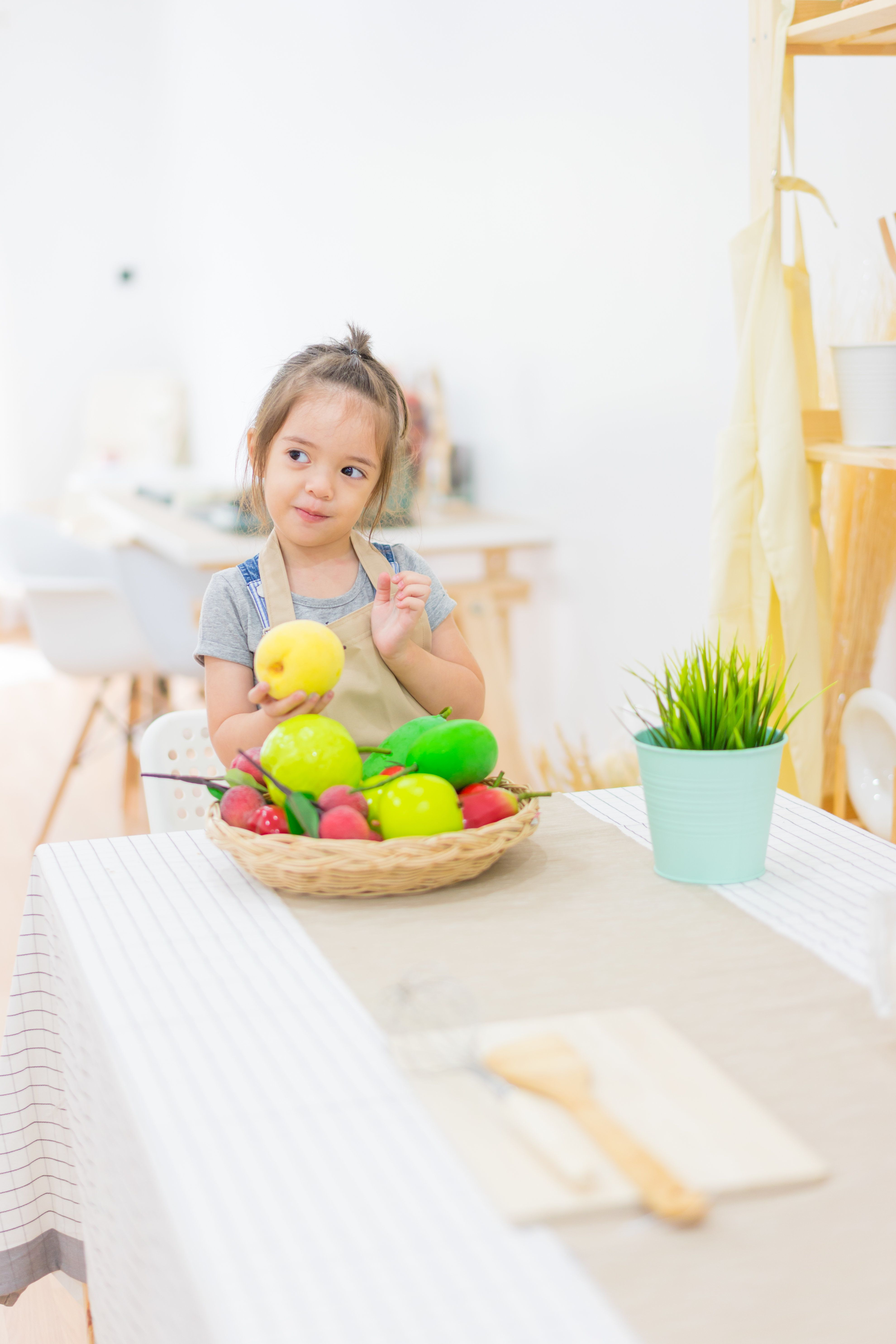 Beautiful little girl with fruits  in basket on kitchen table at house