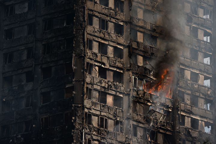 Debris falls from the burning 24 storey residential Grenfell Tower block in Latimer Road, West London on June 14, 2017 in Lon