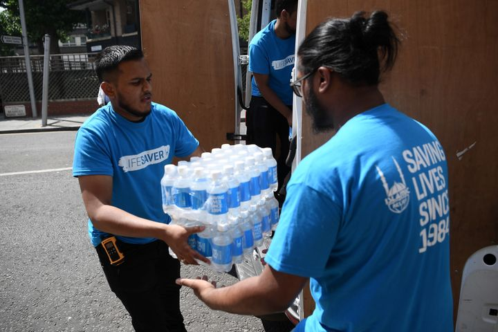 Islamic Relief charity workers arrive with bottled water near the 24 storey residential Grenfell Tower block in Latimer Road, West London on June 14, 2017 in London, England.