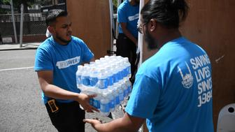 LONDON, ENGLAND - JUNE 14:  Islamic Relief charity workers arrive with bottled water near the 24 storey residential Grenfell Tower block in Latimer Road, West London on June 14, 2017 in London, England.  The Mayor of London, Sadiq Khan, has declared the fire a major incident as more than 200 firefighters are still tackling the blaze, while at least 50 people are receiving hospital treatment.  (Photo by Carl Court/Getty Images)