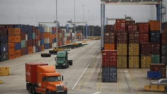 Trucks drive through the container yard at the Port of Charleston in Charleston, South Carolina, U.S., on Thursday, Dec. 17, 2015. The U.S. Census Bureau is scheduled to release international trade balance figures on December 29. Photographer: Luke Sharrett/Bloomberg via Getty Images