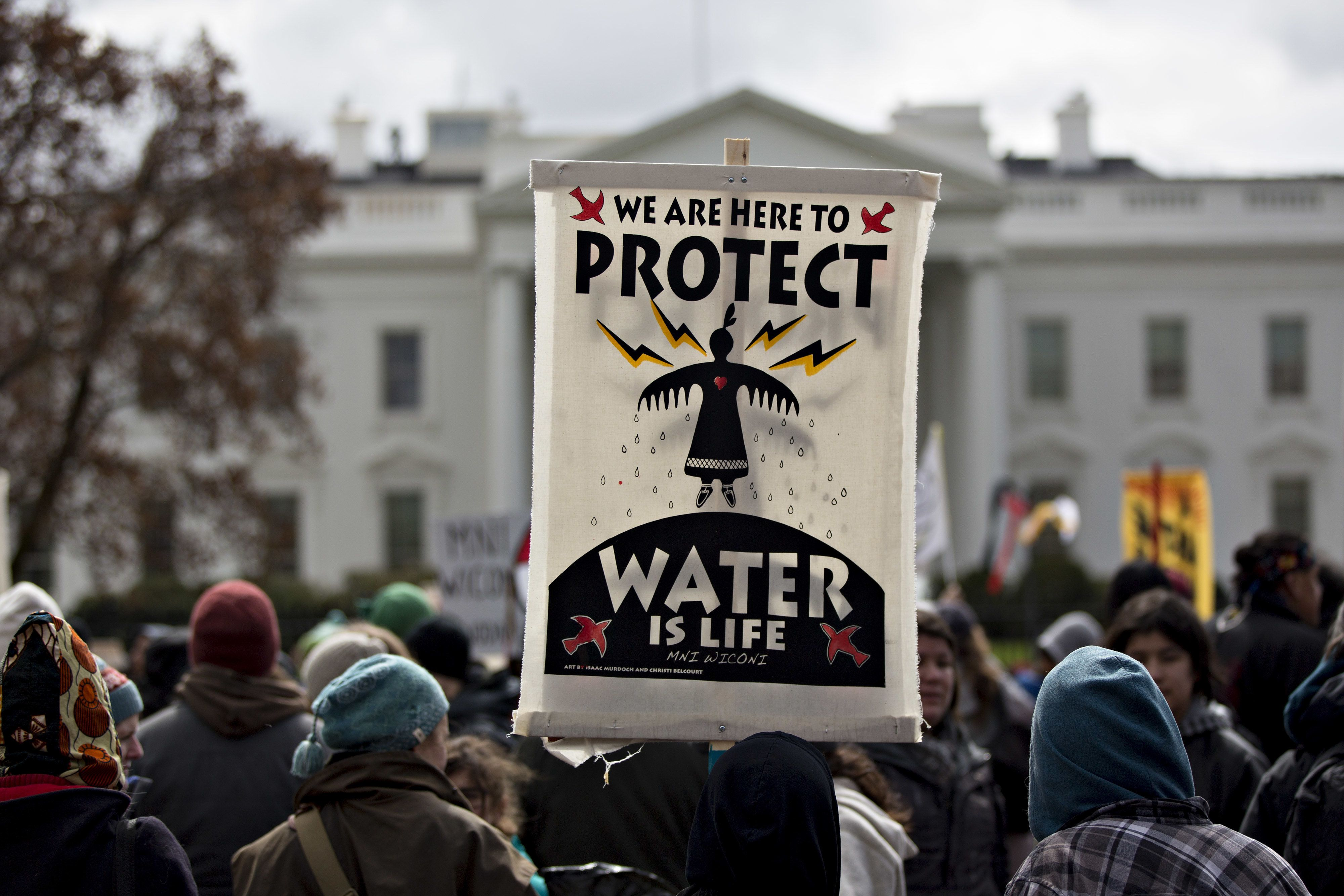A demonstrator holds a 'Water Is Life' sign in front of the White House during a protest against the Dakota Access Pipeline (DAPL) in Washington, D.C., U.S., on Friday, March 10, 2017. The Standing Rock Sioux Tribe and Indigenous grassroots leaders arranged for the march to protect native sovereignty, keep fossil fuels in the ground and stop construction of the DAPL project. Photographer: Andrew Harrer/Bloomberg via Getty Images