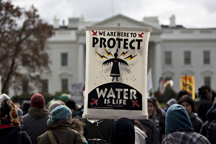 A demonstrator holds a 'Water Is Life' sign in front of the White House during a protest against the Dakota Access Pipeline i