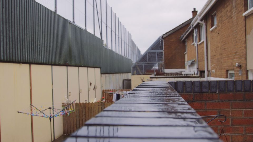 The 10ft Peace Line and protected gardens of houses in a Catholic area of the