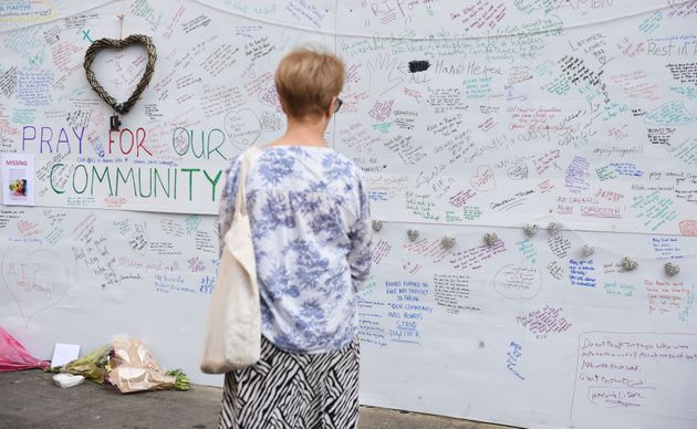 A woman reads a wall of tributes close to Grenfell