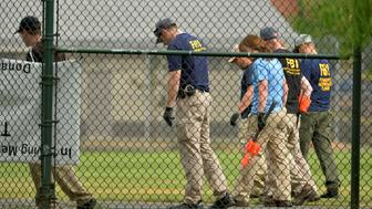 FBI technicians walk in close formation as they examine the outfield area of a baseball field for evidence where shots were fired during a Congressional baseball practice wounding House Majority Whip Steve Scalise (R-LA), in Alexandria, Virginia, U.S., June 14, 2017.              REUTERS/Mike Theiler