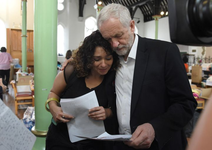 Britain's oppositon Labour Party leader Jeremy Corbyn meets a local resident at St Clement's Church, following a fatal fire i