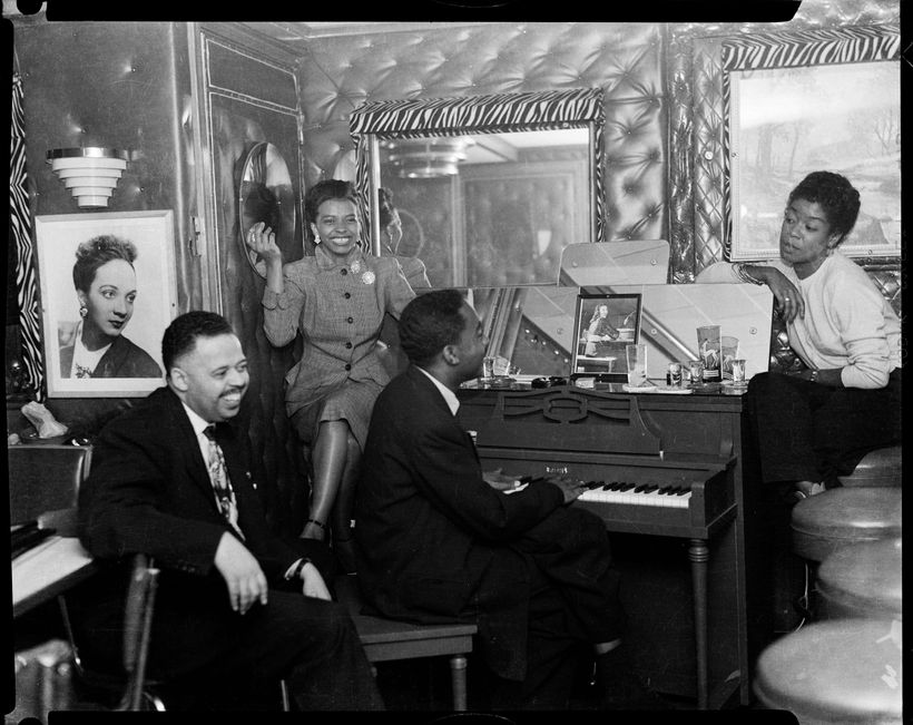 Frank Bolden, unknown woman, man playing piano, and Sarah Vaughan on right, in club with upholstered walls, zebra striped tri