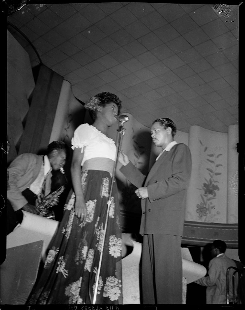 Billy Eckstine conducting his orchestra with Sarah Vaughan in flowered skirt at microphone, and Charlie Parker on saxophone i