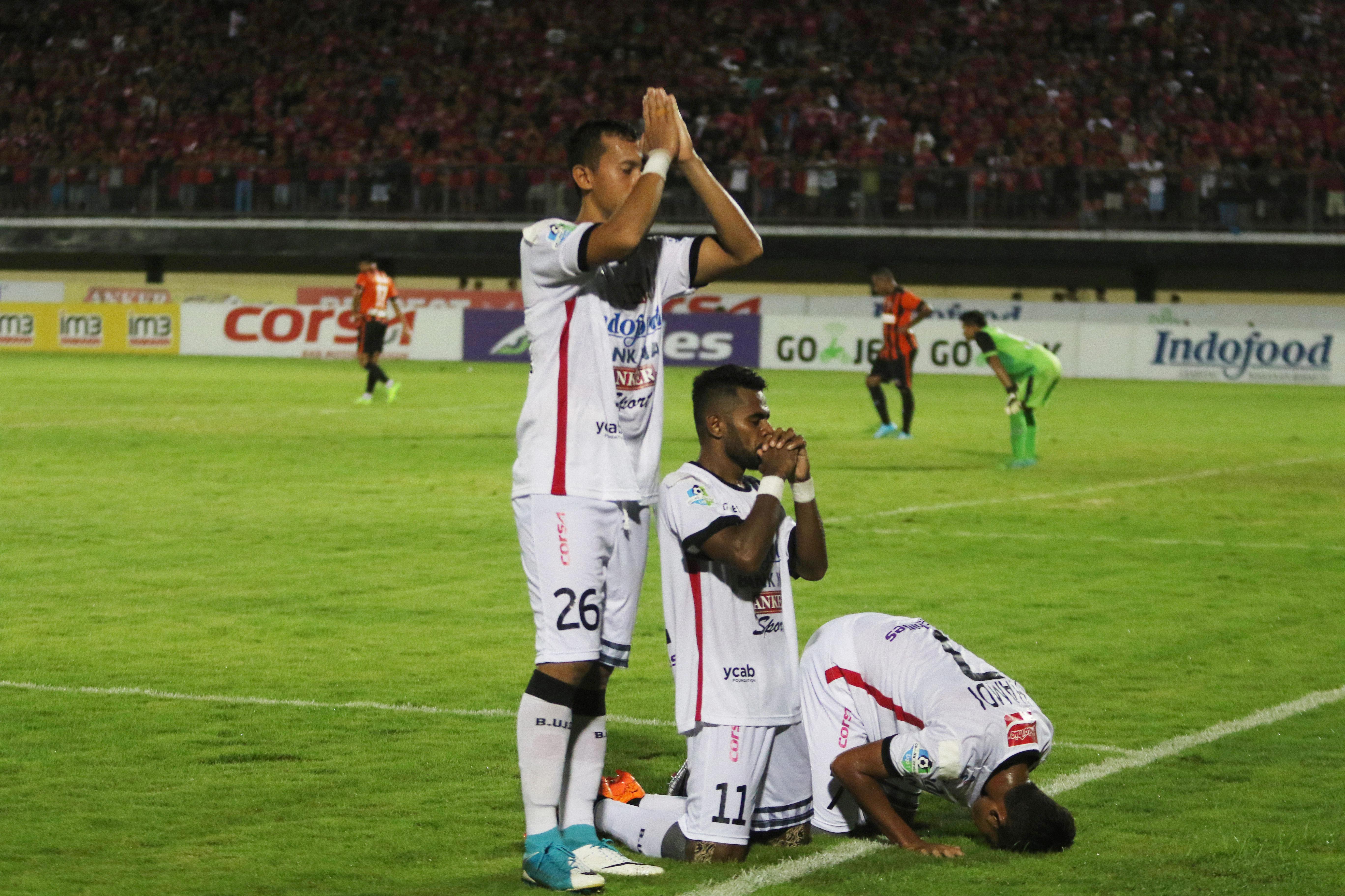 Bali United soccer players Ngurah Nanak, Yabes Roni and Miftahul Hamdi pray regarding their religion as they celebrate goals