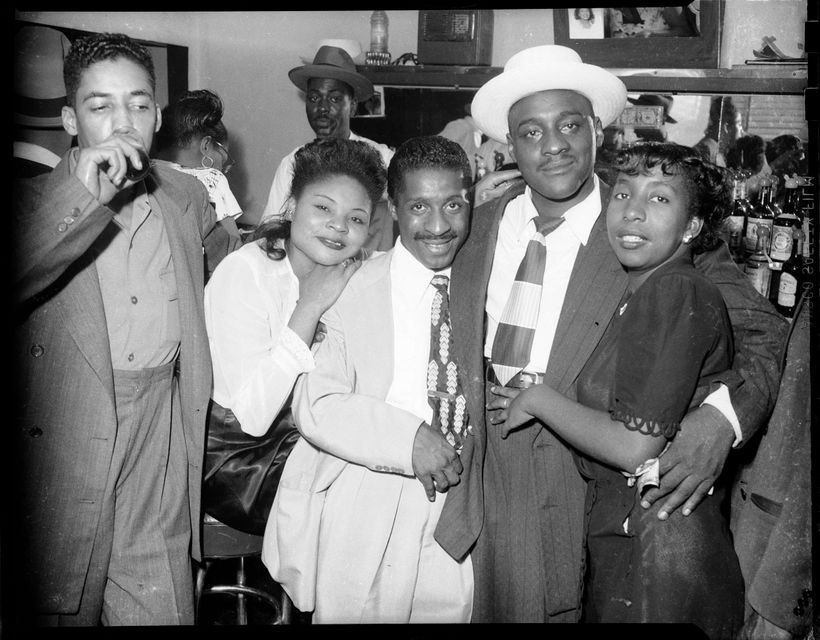 Women and men posed with arms around each other, including Erroll Garner wearing light colored suit in center, in bar or club