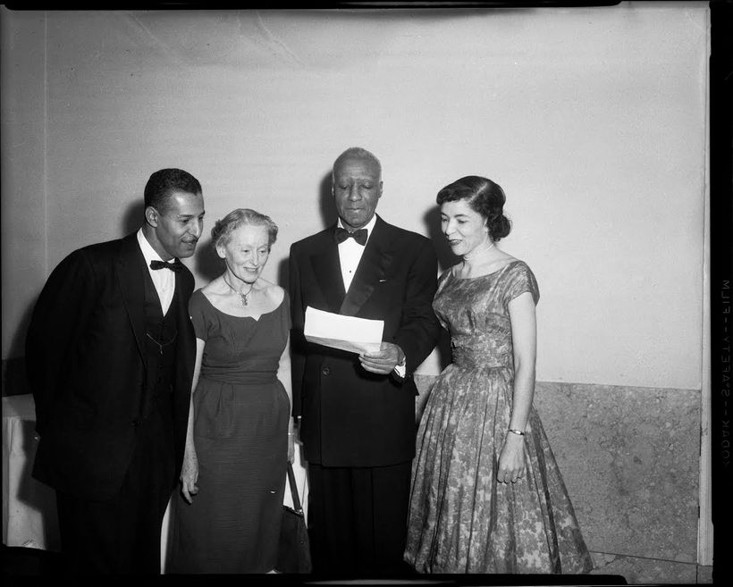 Rev. Charles Foggie, Florence Reizenstein, A. Philip Randolph holding document, and Marion Bond Jordan, standing in interior