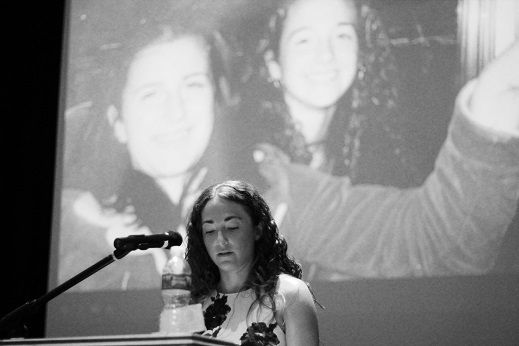 <p>A photo of Cook with her cousin, Jessica, projects on the screen behind her.</p>