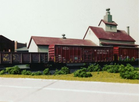 <em>One of the very few photos we have of one of Dad's many different scaled model train set layouts; he painted or placed ev