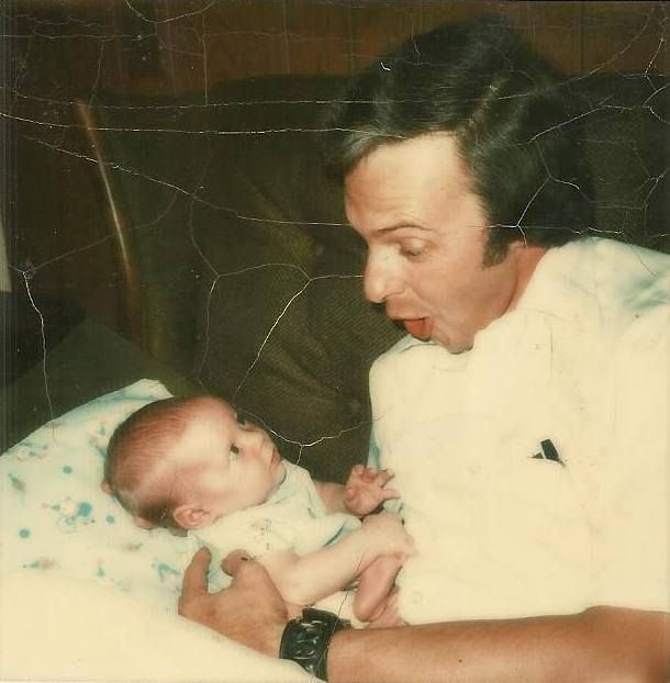 <em>Dad, trying to elicit a smile from me as a newborn, July 1974</em>