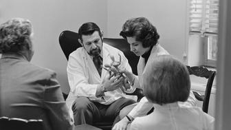 Doctor and Woman Holding Dolls at Sex Clinic (Photo by © Wally McNamee/CORBIS/Corbis via Getty Images)