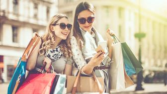 Cheerful beautiful women are shopping in the city. They are using smart phone, and one of them is holding a credit card.