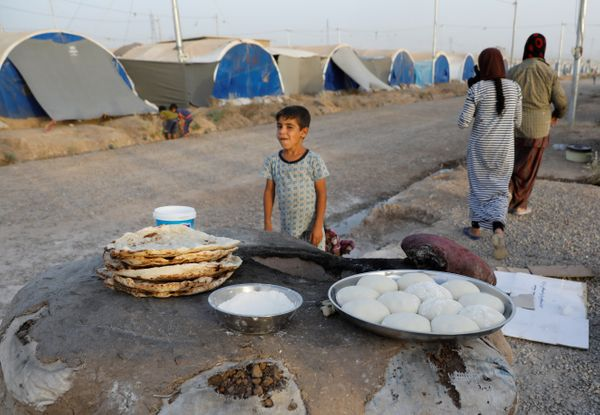 Displaced Iraqi family from Mosul bake bread for their Iftar, during the Muslim holy month of Ramadan at a refugee camp al-Kh