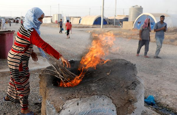 A displaced Iraqi woman from Mosul use fire to heat a makeshift oven to bake bread for Iftar, during the Muslim holy month of