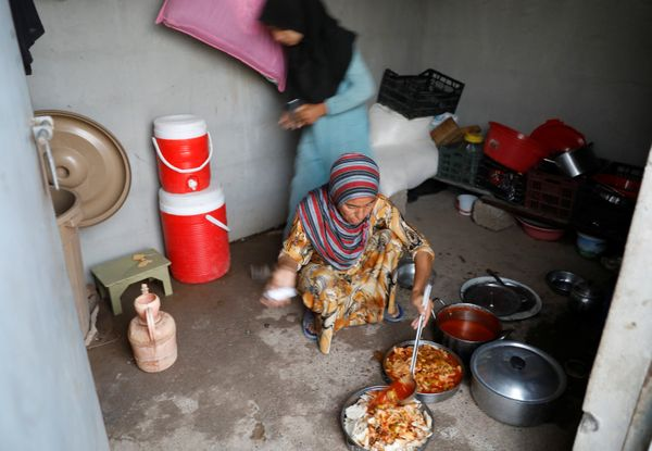 A displaced Iraqi woman from Mosul prepares food for her family's Iftar at a refugee camp at al-Khazir in the outskirts of Er