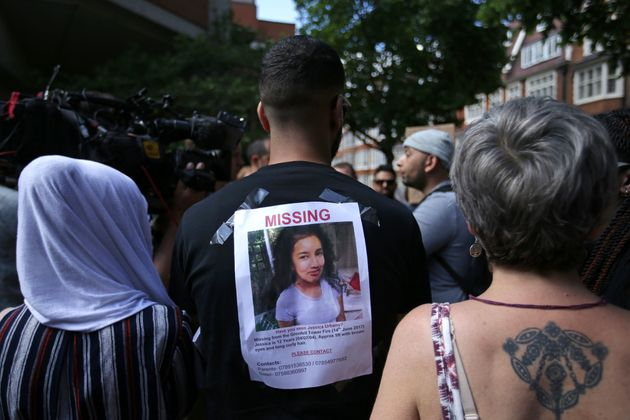 A man carries a picture of a missing person on his back at the