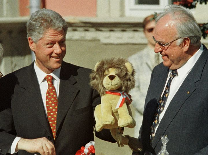 President Bill Clinton (L) displays a toy lion as German Chancellor Helmut Kohl (R) looks on after Clinton received a basket