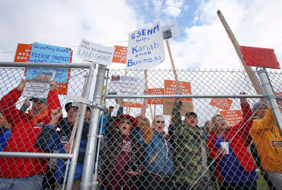 Protesters hold signs and chant behind a security fence as U.S. Secretary of the Interior Ryan Zinke...