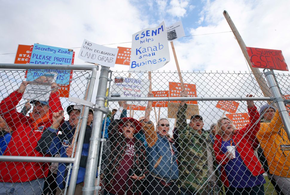 Protesters hold signs and chant behind a security fence as U.S. Secretary of the Interior Ryan Zinke arrives at Kanab Airport