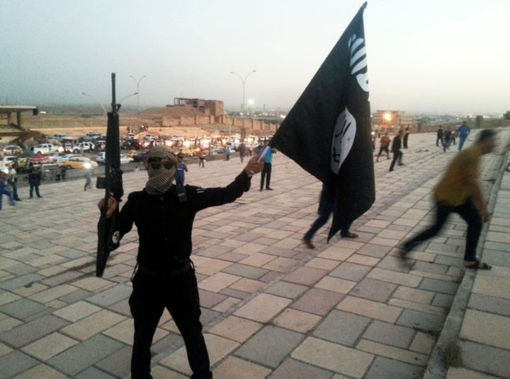 A member of the Islamic State of Iraq and the Levant holds an ISIL flag and a weapon in the city of Mosul on June 23, 2014.