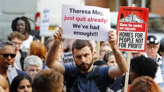 A protester stands with a placard demanding 'Theresa May, just quit already! We've had enough!!!' outside the Department for Communities and Local Government in central London on June 16, 2017 to demand justice for those affected by the Grenfell Tower fire. Dozens of people are feared dead in the London tower block fire as emergency workers continued searching for bodies in the high-rise on Friday, warning they may never be able to identify some of the victims. / AFP PHOTO / Tolga AKMEN        (Photo credit should read TOLGA AKMEN/AFP/Getty Images)