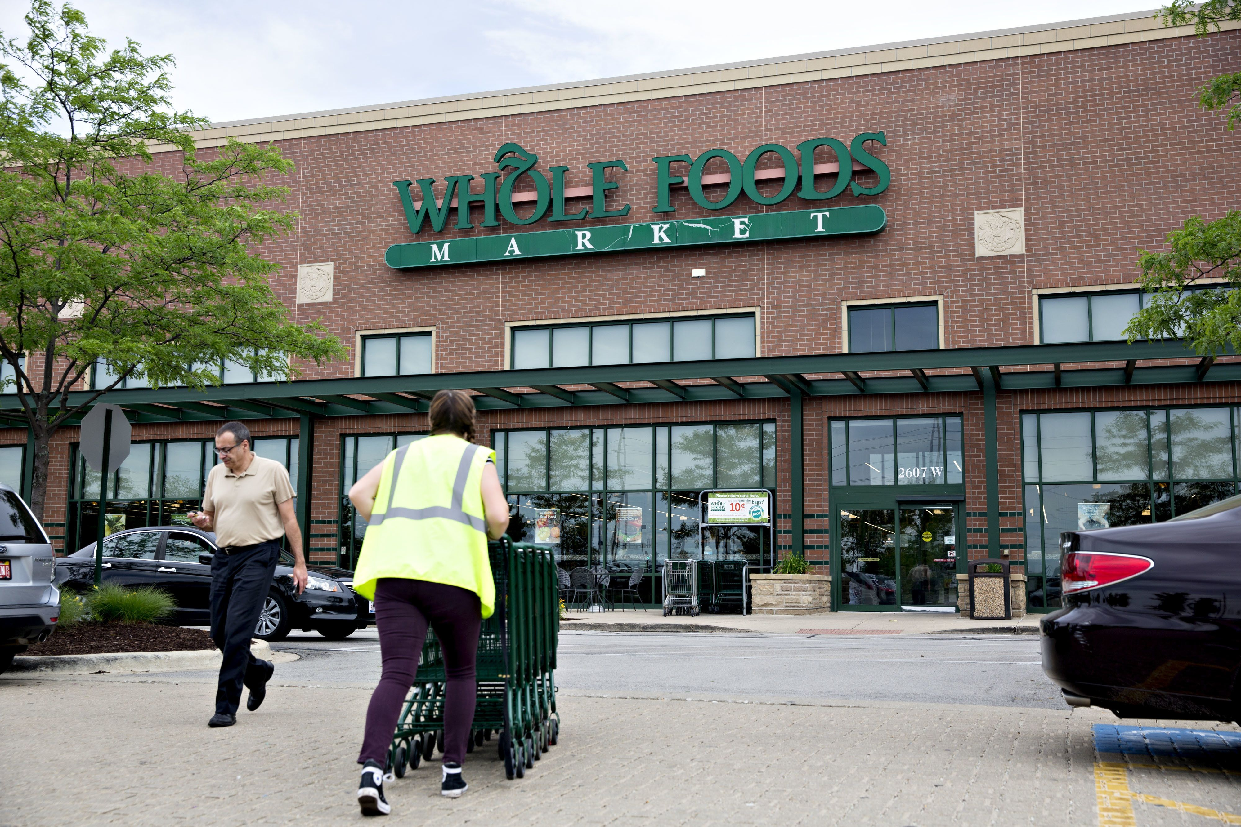 An employee pushes shopping carts outside a Whole Foods Market Inc. location in Naperville, Illinois, U.S., on Friday, June 16, 2017. Amazon.com Inc. will acquire Whole Foods Market Inc. for $13.7 billion, a bombshell of a deal that catapults the e-commerce giant into hundreds of physical stores and fulfills a long-held goal of selling more groceries. Photographer: Daniel Acker/Bloomberg via Getty Images