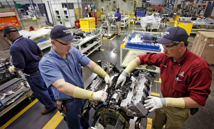 Employees disassemble a motor in the quality control department of the Toyota Motor Manufacturing plant in Huntsville, Alabam