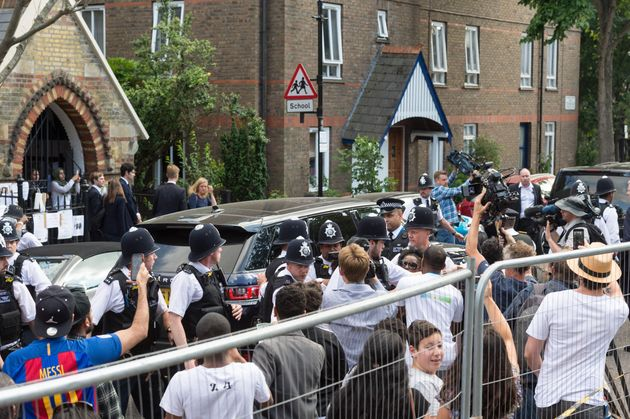 Police protect the PM's entourage as angry resident harangue her after meeting survivors of the