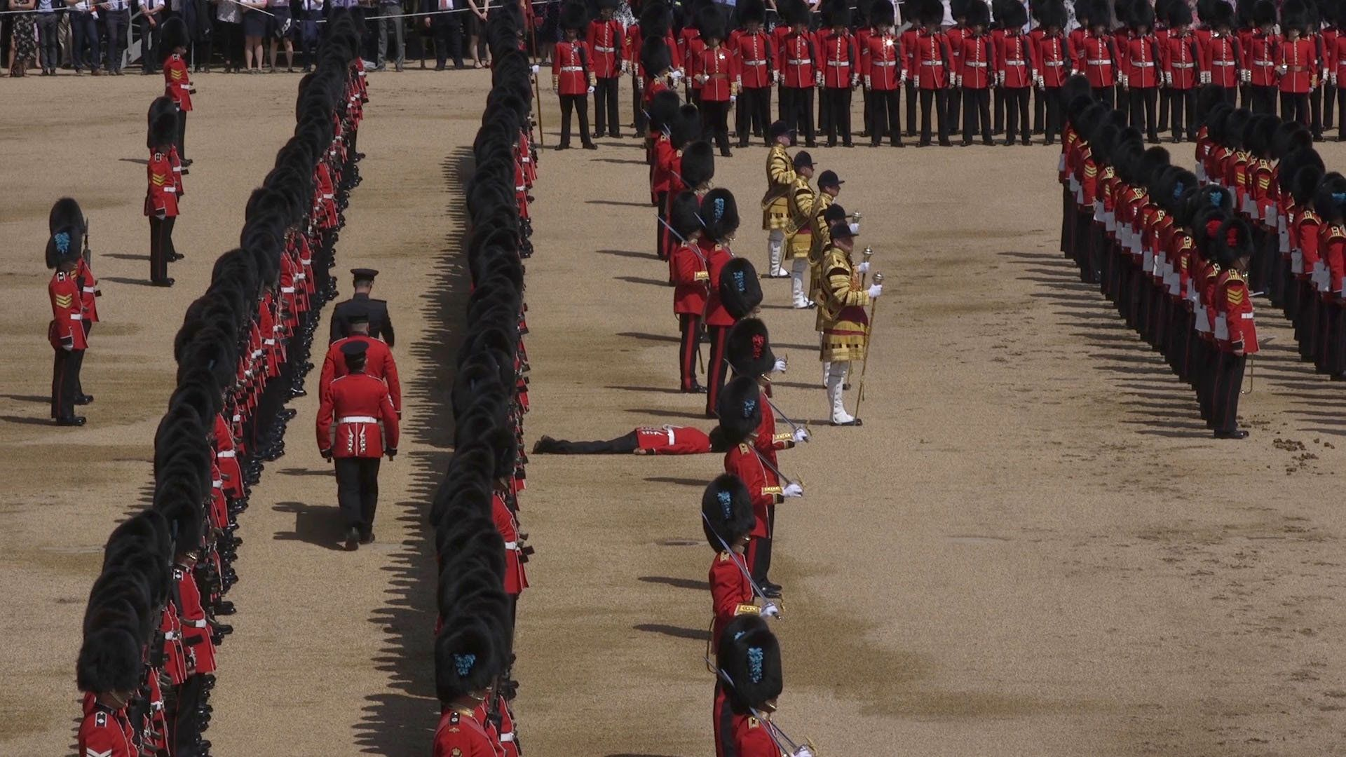 A Guardsman lies prone after fainting during the Trooping the Colour ceremony at Horse Guards Parade,...
