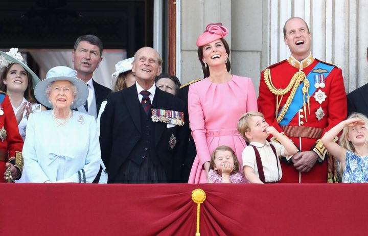 The royal family watching a fly by by a Royal Air Force plane.