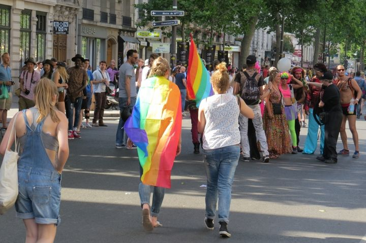 Two people face away from the camera and walk towards a larger group. The person on the left is draped in a rainbow flag.