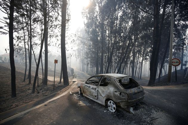 A burned car is seen in the aftermath of a forest fire near Pedrogao Grande, in central Portugal, June...