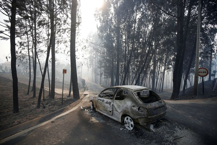 A burned car is seen in the aftermath of a forest fire near Pedrogao Grande, in central Portugal, June 18, 2017. (REUTERS/Raf