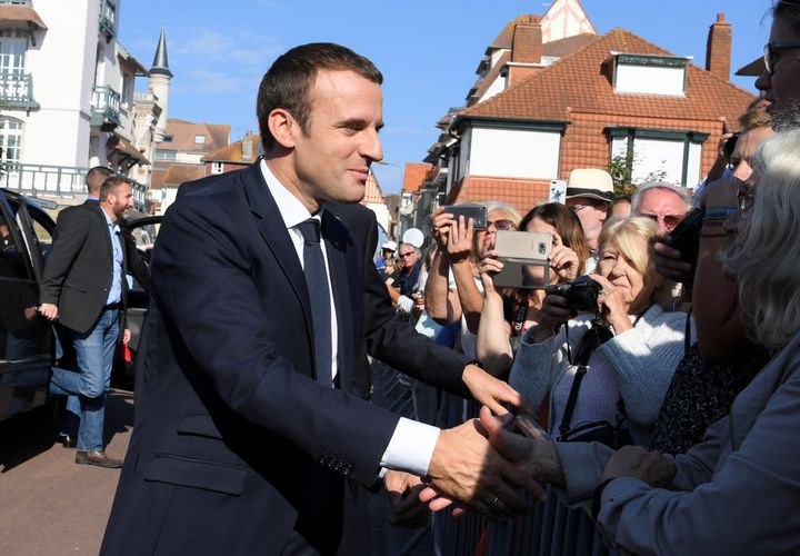 French President Emmanuel Macron (L) shakes hands with people outside the city hall where he votes in the second round of par