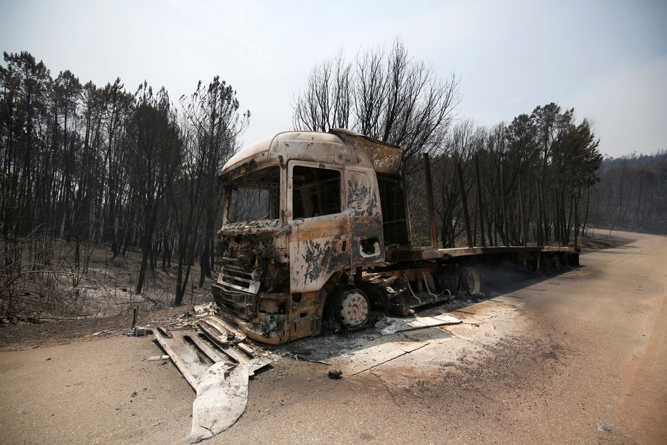 A burned truck is seen during a forest fire near Figueiro dos Vinhos,