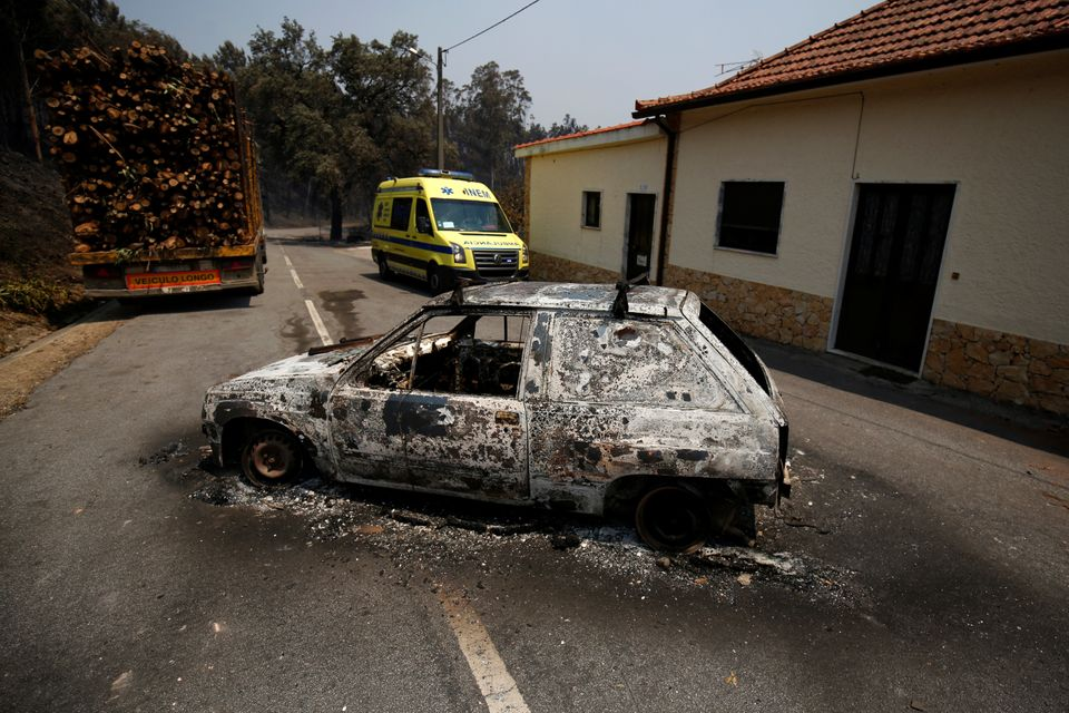 An ambulance drives past a burned car during a forest fire in Figueiro dos