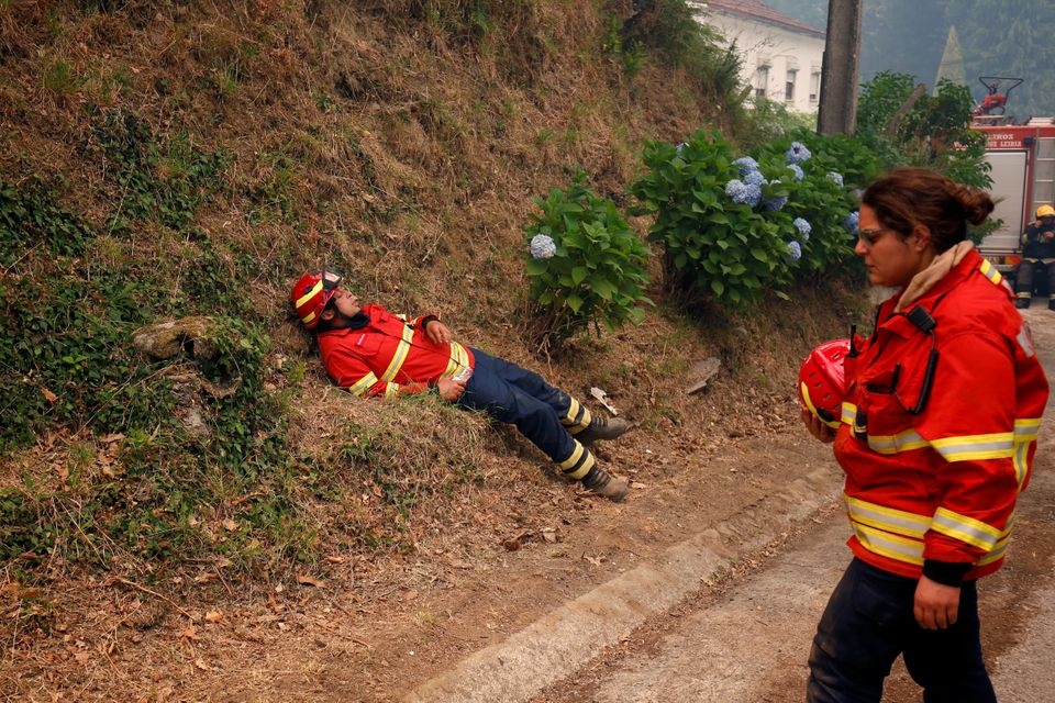Firefighters rest during a forest fire near the village of Torgal,