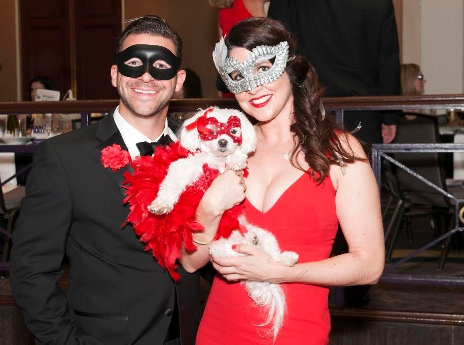 This dashing trio came dressed to the nines with the four-legged partygoer wearing red feathers and a mask