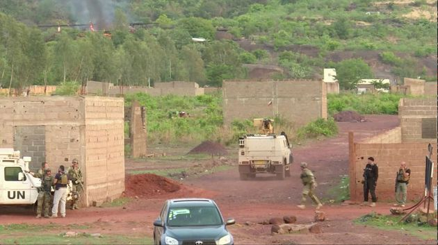 An armoured vehicle drives towards Le Campement Kangaba resort following an attack where gunmen stormed...