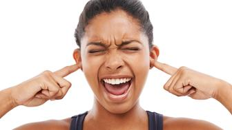 A frustrated young woman blocking her ears while isolated on a white background
