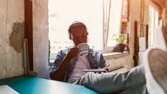 African man podcasting in modern office. Sitting with headphones, with feet up on table and writing